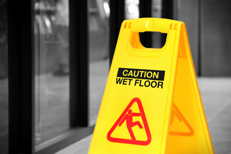 Bright yellow caution sign of wet floor in a hallway. Conceptual image with isolated color over black and white background 写真素材