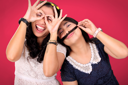 friends together: Two happy female best friends posing to camera with crazy gleeful expressions, over hot pink background