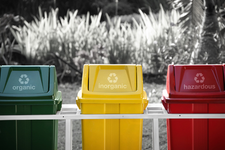 grayscale background: Colorful recycle bins in a park, separated with labels. Conceptual image with isolated color over grayscale background