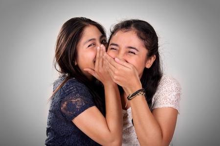 mejores amigas: Amigas asiáticas chismes. Una niña riendo cuando su amiga susurra algo divertido Foto de archivo