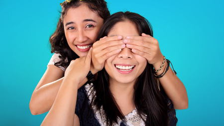 Two smiling Asian female friends play guess who game. One girl covering her friends eyes from behind, over blue background