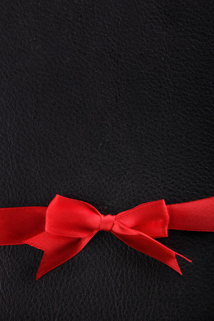 ties: A red ribbon on the lower side of black leather background