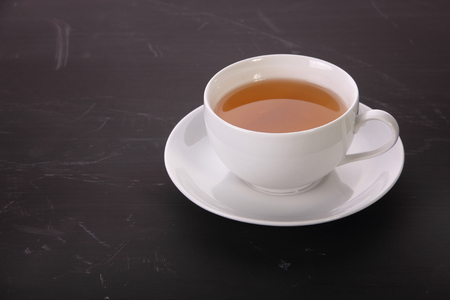 A cup of tea in saucer on top of dark textured table Stock Photo