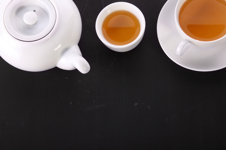 english breakfast tea: Overhead shot of tea pot and cups placed on top of the frame, over dark textured background for copy space