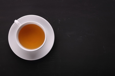 break: A cup of tea shot from the top, on the left side of composition in black board surface with copy space
