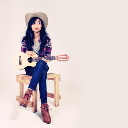 Vintage color portrait of country style girl posing with her small guitar on a chair
