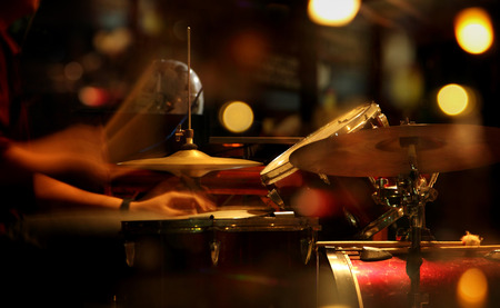Scenic portrait of a jazz drummer playing in a nightclub. Conceptual blurred image with colorful light illumination
