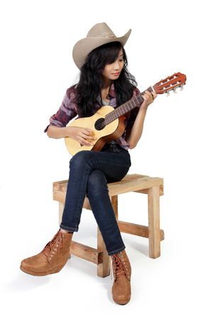 cowgirl boots: Cowgirl playing ukulele on a wooden chair, isolated on white background Stock Photo