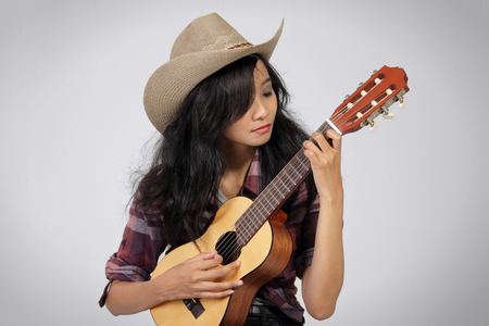 acoustic ukulele: Portrait of young attractive woman wearing cowboy hat playing ukulele with closed eyes