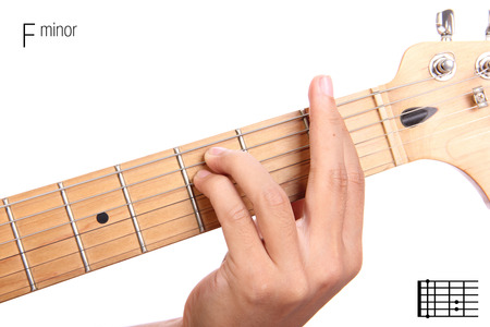 fm: Fm - basic minor keys guitar tutorial series. Closeup of hand playing F minor chord on guitar, isolated on white background Stock Photo