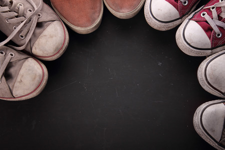Overhead shot of some dirty sneakers' tips making a circle for copy space on black textured background
