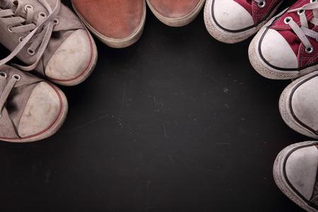pieds sales: tir aérien des conseils de certains baskets sales faisant un cercle pour copie espace sur fond noir texturé Banque d'images