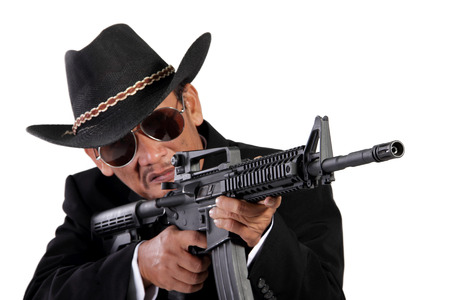 menacing: A menacing old gunman using his assault weapon, isolated on white background Stock Photo