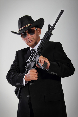 scoundrel: Portrait of an old gangster dressed in black, posing with his machine gun Stock Photo