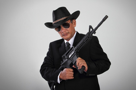 An old mafia in black suit and cowboy hat posing with an assault weapon
