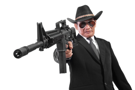 An evil gangster shooting with firearm in his hand, low angle closeup portrait, isolated on white background