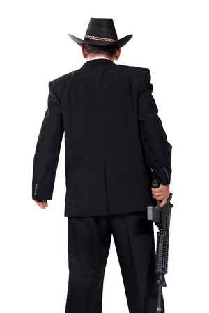 gunman: Back-shot of a gunman in black suit, standing and carrying a rifle, isolated on white background