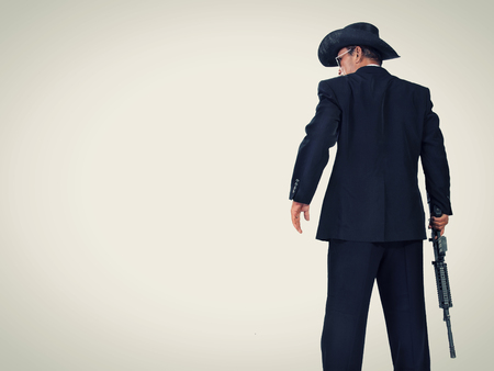 vigilante: Old classic western style hitman standing with a gun, back-shot portrait in vintage color with copy space