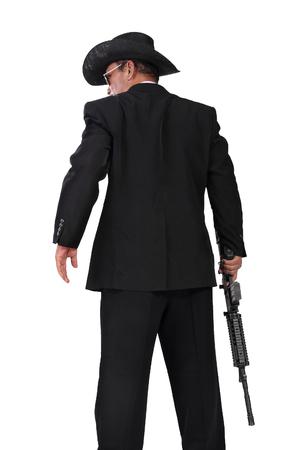 白い背景に分離されて、彼の手に銃を持つ洋風ヒットマン立ってのバック ショット