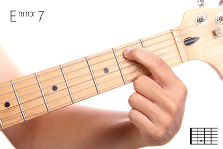 e guitar: Em7 - minor seventh keys guitar tutorial series. Closeup of hand playing E minor seventh chord on guitar, isolated on white background