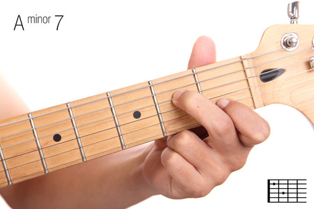 seventh: Am7 - minor seventh keys guitar tutorial series. Closeup of hand playing A minor seventh chord on guitar, isolated on white background