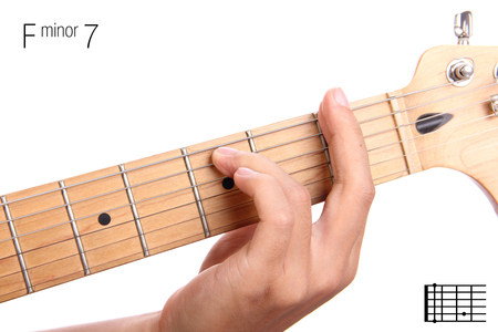 seventh: Fm7 - minor seventh keys guitar tutorial series. Closeup of hand playing F minor seventh chord on guitar, isolated on white background