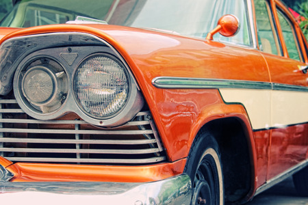 Closeup of oldtimer car with orange colored paint on automobile show