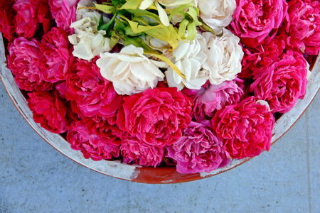 Overhead closeup on a basket of roses petals for religious ceremony in Bali