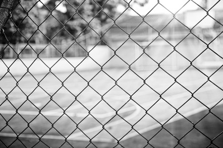 prison yard: View of a basketball court through the fence, in black and white