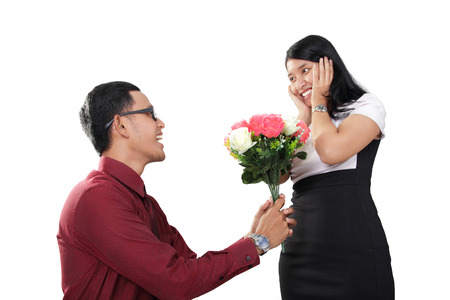 kneel down: Young Asian man kneel down and gives flowers to her surprised girfriend, isolated on white background Stock Photo