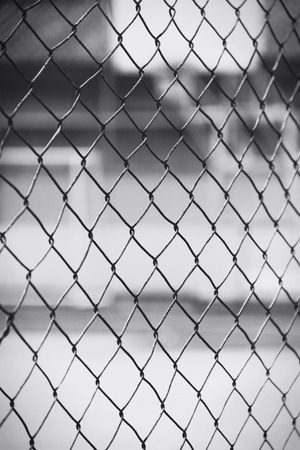 prison yard: Closeup of metal wire on basketball court, in black and white Stock Photo