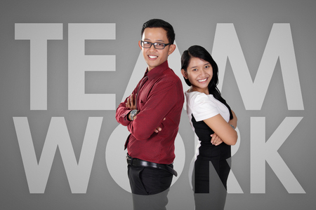 coworker: Team Work. Conceptual business illustration with typeface graphic and image of happy confident business couple Stock Photo
