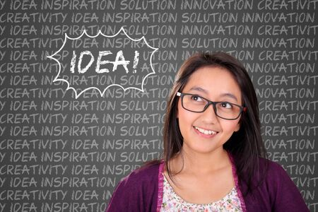 woman looking up: Smiling Asian woman looking up at the word Idea above her, in chalkboard typography words cloud concept background