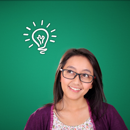 bright colors: Happy Asian woman looking up at hand drawn lightbulb doodle on the top, over green background Stock Photo