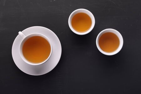 Some tea cups arranged on black board surface, view from the top