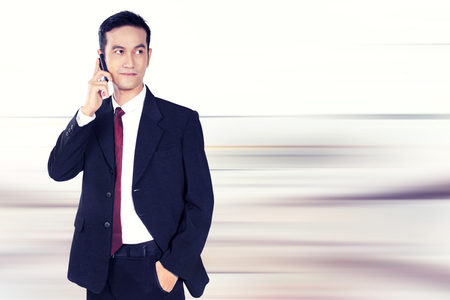 confidently: Young handsome business man using mobile phone and looking to the side confidently, over abstract background