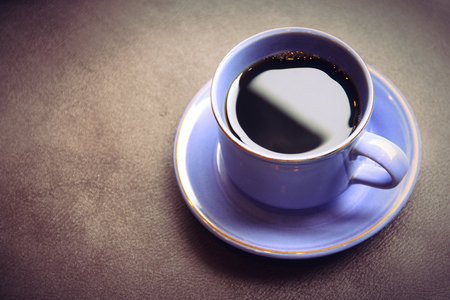 A cup of coffee on textured table, close up image in vintage color filter
