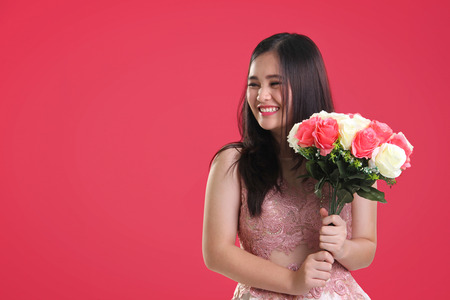 sweet seventeen: Sweet cheerful Asian teenage girl with natural smile holding a bouquet of roses, looking sideways at copy space on pink background for Valentines Day