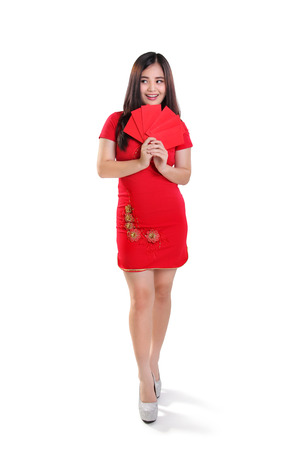 Full body portrait of happy young Asian female model wearing cheongsam dress, holding red envelopes and looking sideways, isolated on white background