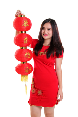 gong xi fa cai: Portrait of gorgeous Asian girl in cheongsam dress raise a red Chinese lantern, isolated on white background
