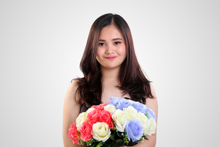 sweet seventeen: Cute Asian teenage girl with innocent smile holding colorful roses bouquet, on white background for Valentine concept