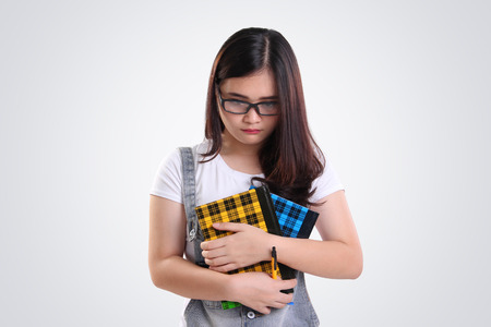 awkwardness: Nerdy Asian school girl looking down with sad depressed face, on white background Stock Photo