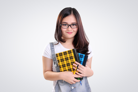 nerd glasses: Adorable Asian nerd teenage girl holding some books and pen, on white background