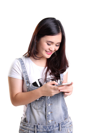 Portrait of cheerful smiling Asian girl using smartphone gadget, isolated on white background Archivio Fotografico