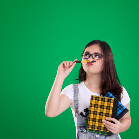 Cute adorable Asian school girl looking up to copy space at the top of green background with silly face Stock Photo