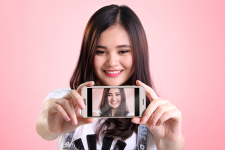 narcissistic: Self shot picture on smartphone screen of cute Asian girl, over pink background