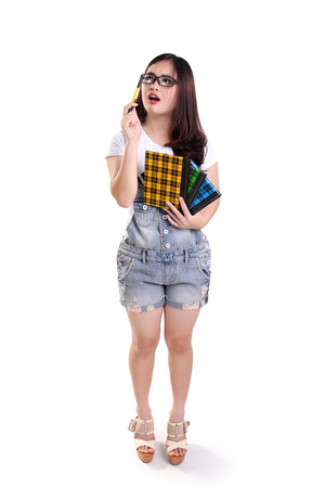 confused face: Full length portrait of geeky school girl looking at something above with confused face, isolated on white background
