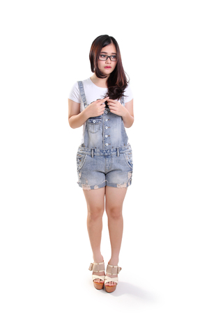 humiliated: Full length portrait of cute shy nerdy girl standing awkwardly, isolated on white background Stock Photo