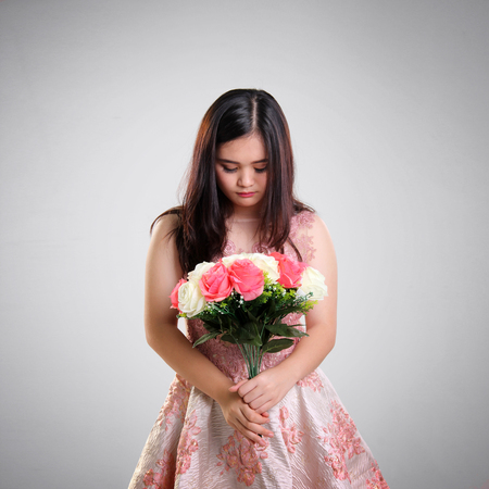 teenage girl dress: Asian teenage girl in a dress holding roses bouquet looking down with sad face expression