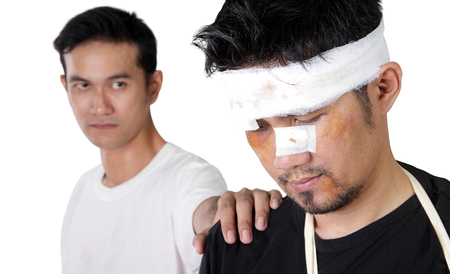 beaten up: Close up portrait of Asian man with beaten up face, and a friend lays hand on his shoulder, isolated on white background Stock Photo